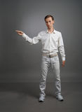 Young man in white shirt is pointing at something, standing on grey background Royalty Free Stock Photo