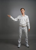 Young man in white shirt is pointing at something, standing on grey background Stock Image