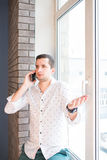 Young man in white shirt speaking over phone with interrogative expression Royalty Free Stock Photo