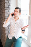 Young man in white shirt speaking over phone with interrogative expression Stock Photos