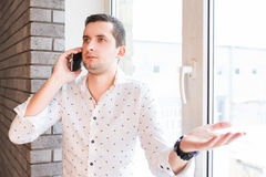 Young man in white shirt speaking over phone with interrogative expression Stock Photo