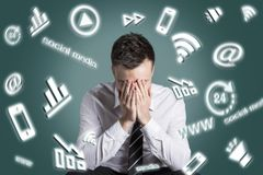 Digital media symbols swirling around an exhausted man stock photo
