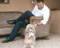 Young man with a white shirt and with trousers siting in a chair. And playing with a dog.  Concepts of friendship. Pets and his owner. The dog is dressed in a Royalty Free Stock Image