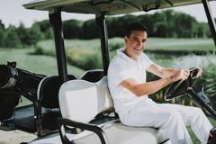 Young Man in White Shirt using Cart on Golf Field. Happy Young Man. Driver with Car. Healthy festyle Concept. Golf Club. Sports in Summer. Vehicle on Field stock photo