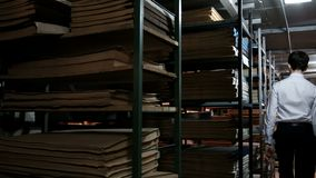 A young man in a white shirt wanders between the shelves of books and looks around. Placing an old library or archive of. A young man in a white shirt wanders stock video footage