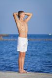 Young man in white shorts at the sea. Guy with arms raised standing on pier looking into distance Stock Images