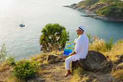 A young man in a white suit sitting on the beach Stock Photography