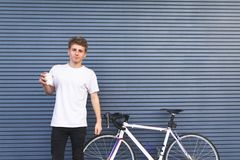 Young man in a white T-shirt stands by a bicycle with a cup of coffee in his hands against the background of a blue wall royalty free stock photography