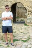 A young man in a white T-shirt and sunglasses stands on the wall of the fortress. 2018 Stock Image