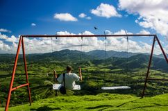 A young man in white T-shirt swinging on a swing. Among the green hills in the Souf-East coast of the Dominican Republic Stock Photo