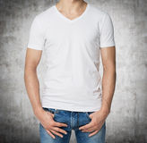 Young man in a white V shape t-shirt, hands in pockets. Stock Image