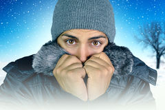 Young man who complains about the cold. On a snowy background royalty free stock photos