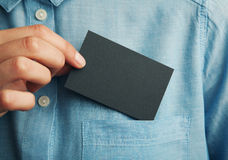 Young man who takes out black blank business card from the pocket of his shirt. Young business man who takes out black blank business card from the pocket of his Royalty Free Stock Photo