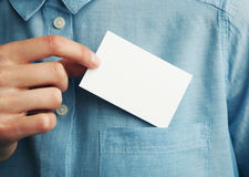 Young man who takes out blank business card from the pocket of his shirt Royalty Free Stock Photography