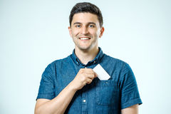 Young man who takes out blank business card from pocket of shirt Royalty Free Stock Photo