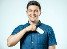 Young man who takes out blank business card from pocket of shirt Royalty Free Stock Photography
