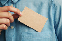 Young man who takes out craft blank business card from the pocket of his shirt. Young business man who takes out craft blank business card from the pocket of his Royalty Free Stock Photos