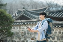 Young man who travels to Korea is taking pictures using his smartphone. A young man who travels to Korea is taking pictures using his smartphone Stock Images