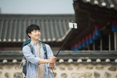 Young man who travels to Korea is taking pictures using his smartphone. A young man who travels to Korea is taking pictures using his smartphone Stock Photos