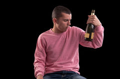 Young man who wants to drink alcohol, read on glass alcohol conc Royalty Free Stock Images