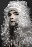 Young man in wig Royalty Free Stock Images