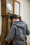 Young man winding the mechanism on a clock Royalty Free Stock Photos