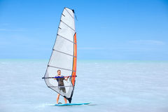 Young man on a windsurf. Young man riding on a windsurf on blue sea royalty free stock photography