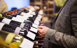 Young man in a wine shop. Unrecognizable young man in a wine shop choosing a wine stock photos