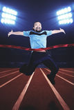 Young man winning the competition on stadium. Young man wearing sportswear, winning the competition and smiling on the stadium Royalty Free Stock Photos