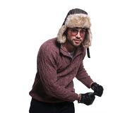 Young man in winter clothes and fur hat is dancing Stock Image