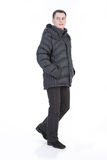 Young Man In Winter Down Clothes. Young man in winter warm down jacket on isolated background stock image