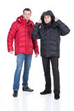 Young Man In Winter Down Clothes. Young man in winter warm down jacket on isolated background stock photo