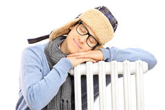 Young man in winter hat sleeping on a radiator Royalty Free Stock Image