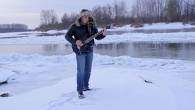 A young man in winter to play the guitar stock video