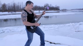 A young man in winter to play the guitar stock video footage
