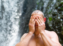 The young man wipes the face after swimming in waterfall. stock photography