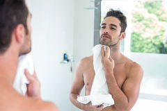 Young man wiping face while looking in mirror Stock Image