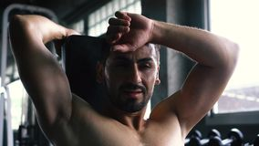 Young man wiping sweat off forehead in gym. Young man wiping sweat off forehead with dumbbells and fitness equipment inside gym. He is tired and exhausted from stock footage