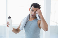 Young man wiping sweat with towel in fitness studio Stock Image