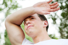 Young man wiping sweaty brow Stock Photo