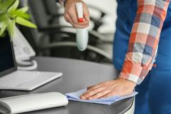 Young man wiping table. In office Stock Image