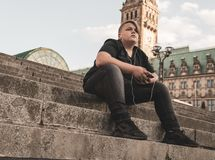 A young man wirh earphones is sitting on steps Stock Image