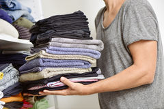 Free Young Man With A Pile Of Folded Clothes Stock Photo - 61376870