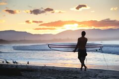 Free Young Man With A Surfing Board Walking On The Shore Of The Sea During Sunset Stock Photography - 190754432