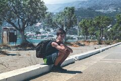 Free Young Man With Backpack Rests On A Curb Stock Images - 175294134