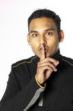 Young Man With Finger Over Mouth Stock Photo