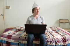Free Young Man With Tin Foil Hat Thinking While Using Laptop In The Bedroom Stock Photo - 162016270