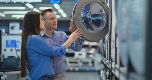 Young man and woman in appliances store choose to buy washing machine for home. Open the door looking into the drum. Compare the design and characteristics of stock footage