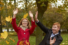 Young man and woman in the autumn park Stock Photos