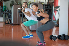 Young man and woman with barbell flexing muscles and making shoulder press squat in gym. Sport, bodybuilding, lifestyle and people concept - young men and women Stock Images